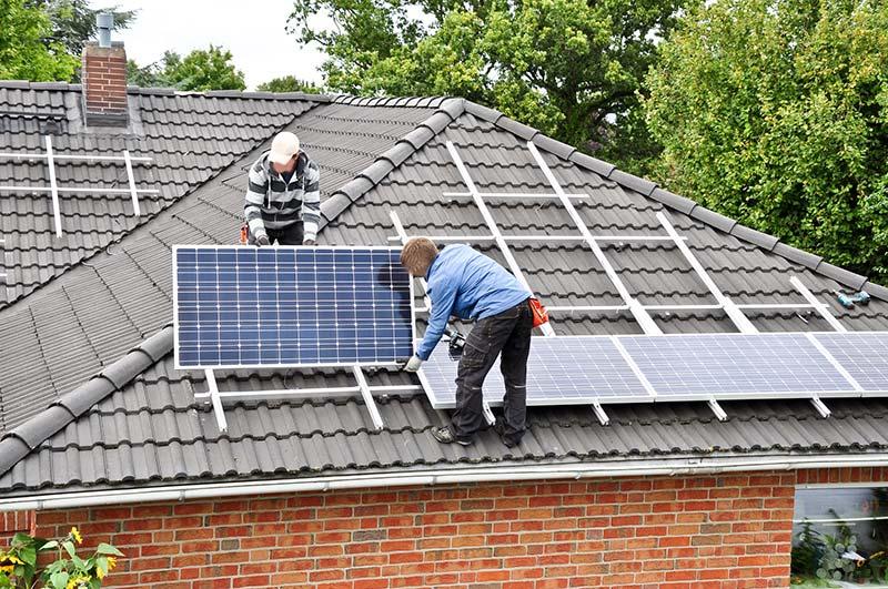 Dwóch mężczyzn nadachu domu jednorodzinnego, montujących panele fotowoltaiczne, zapewniające opłacalny prąd.