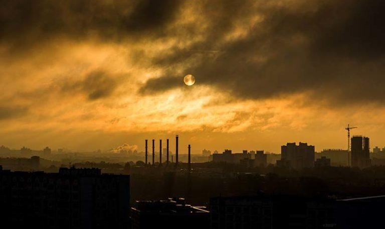Smog nadmiastem - widoczne wysokie budynki orazkominy, zktórychwydobywają się zanieczyszczenia.